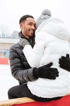 Привлекательные влюбленная пара на коньках на катке на открытом воздухе и обниматься.