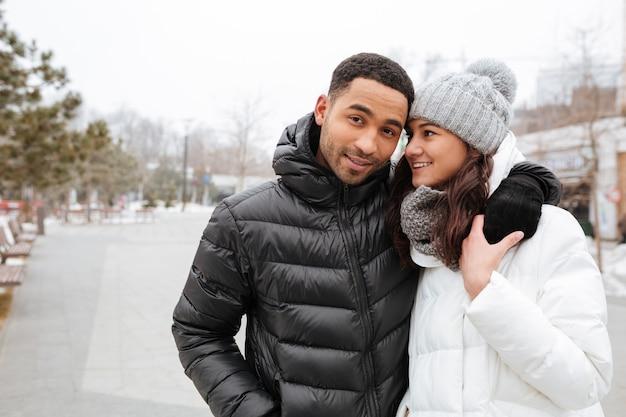 Счастливая многонациональная молодая пара обниматься в зимнем парке