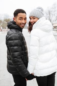 手を繋いでいるカップルと冬の屋外を振り返って