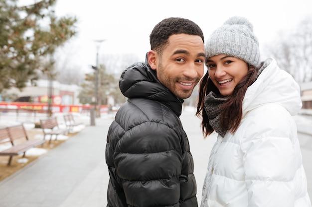 屋外に一緒に立っている笑顔の多民族の若いカップル