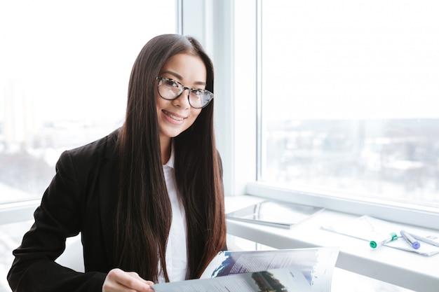 窓の近くのアジアビジネスの女性の笑顔