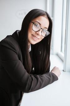 窓の近くのアジアビジネス女性の垂直方向の画像