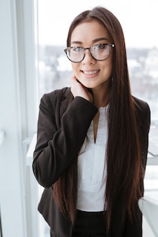 立っていると窓の近く笑顔の眼鏡で幸せな女性実業家