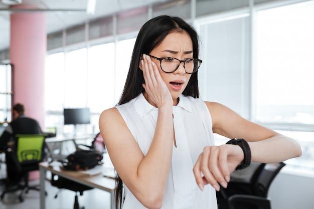 Изумленная потрясенная коммерсантка смотря наручные часы в офисе