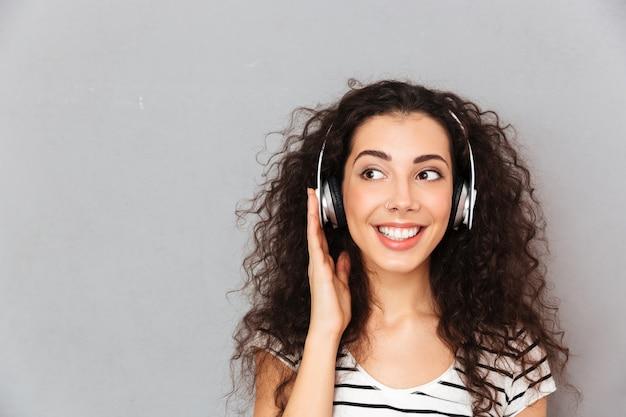 Великолепная картина кудрявой кавказской женщины в полосатой футболке в наушниках, наслаждаясь музыкой через современное устройство во время отдыха