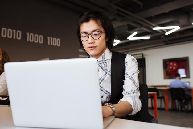 ラップトップコンピューターを使用して集中している若いアジア人