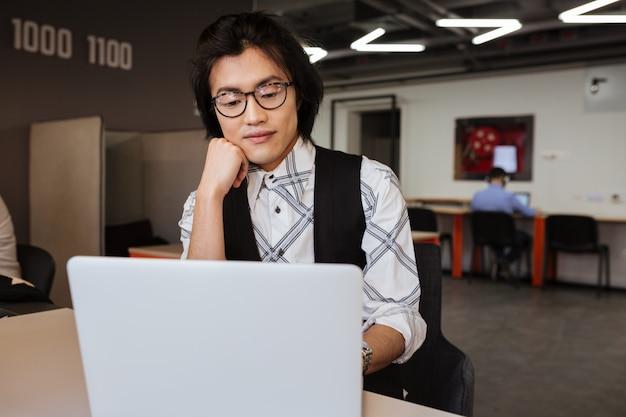 ラップトップコンピューターを使用して眼鏡をかけている深刻な若いアジア人