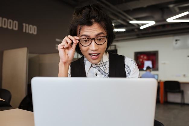 Сотрясенный молодой азиатский человек используя портативный компьютер.