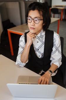 ラップトップコンピューターを使用してハンサムな若いアジア人。