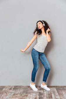 Полноразмерный вид очаровательной молодой женщины в полосатой футболке и джинсах, танцующих во время прослушивания мелодий через наушники над серой стеной