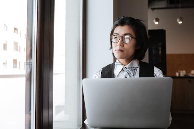 室内でラップトップコンピューターを使用してハンサムな若いアジア人