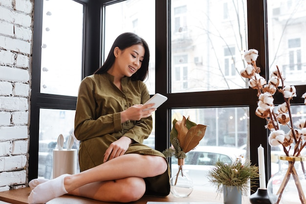 彼女の携帯電話でチャット陽気なアジアの若い女性