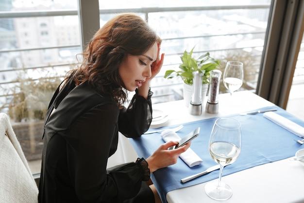 電話を使用してレストランで不機嫌な女性の側面図