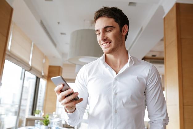 電話でチャットカフェに立っているハンサムな幸せな若い男。