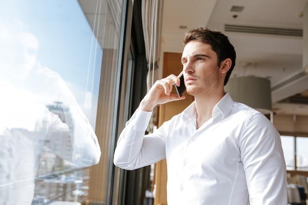 携帯電話で話しているハンサムな深刻な若い男。