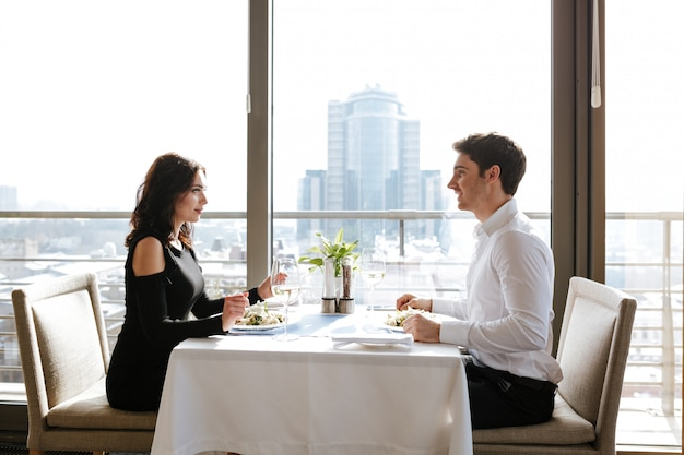 屋内レストランに座っている愛情のあるカップル
