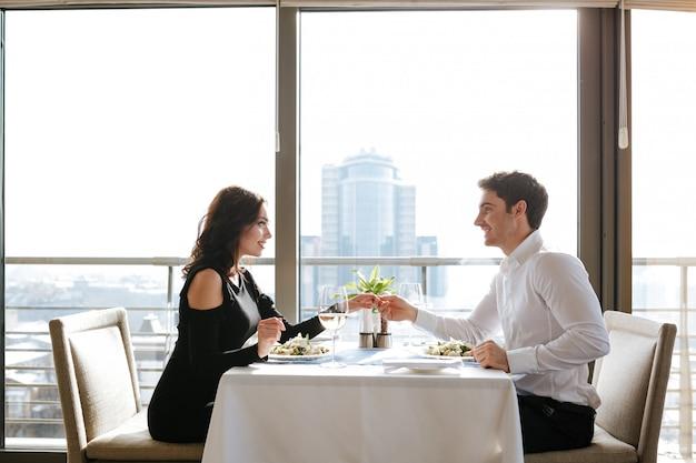 屋内レストランに座って幸せな愛情のあるカップル
