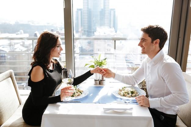 レストランに座っている陽気な愛情のあるカップル