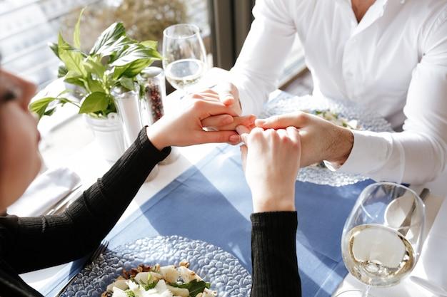 お互いの手を繋いでいる愛情のあるカップルのトリミングされた画像。