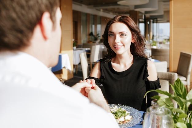 屋内のレストランに座っている笑顔の愛情のあるカップル