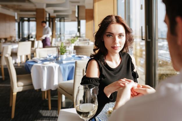 話しながら屋内のレストランに座っている愛情のあるカップル