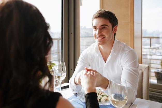 話しながら屋内でレストランに座っている笑顔の愛情のあるカップル