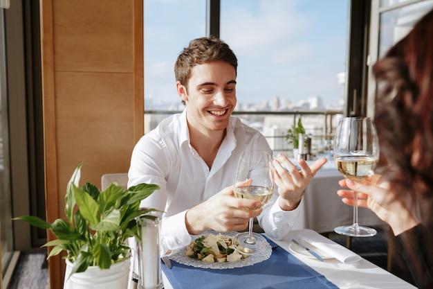 話しながら屋内のレストランに座っている陽気な愛情のあるカップル。