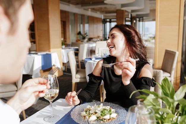 話していると食べながらレストランに座っている愛情のあるカップル