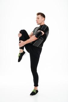 Полнометражный портрет молодого здорового спортсмена протягивая ноги