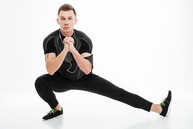 Портрет красивый спортсмен делает упражнения на растяжку перед бегом