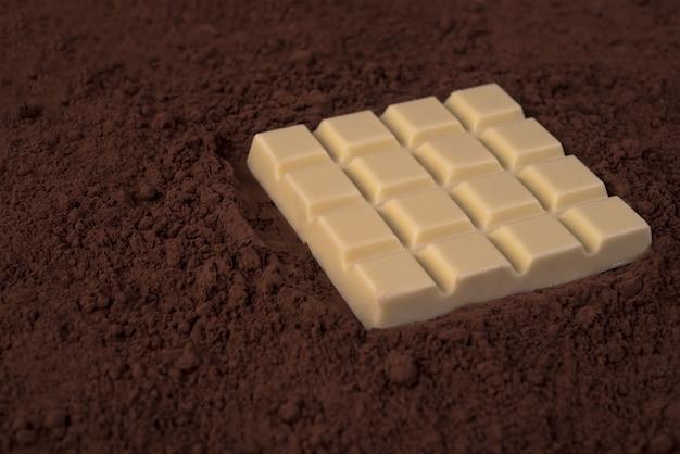 ミルクチョコレートパウダー上のホワイトチョコレートバー
