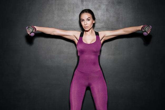 ダンベルとトレーニングを保持している深刻な強い女性