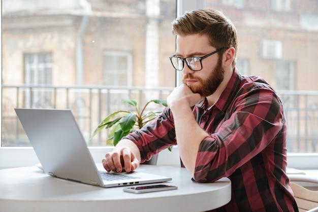 ラップトップコンピューターを使用して深刻なひげを生やした若い男。