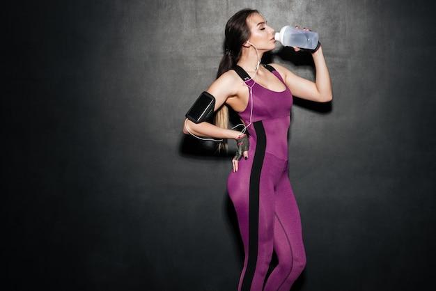 Изолированная питьевая вода женщины и слушая музыка