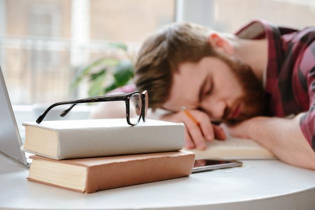 Спящий бородатый молодой человек студент лежит на руках