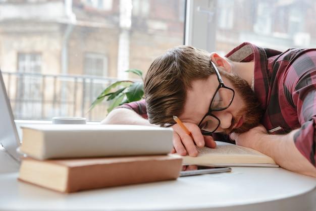 Скучающий бородатый молодой человек в очках лежит на руках