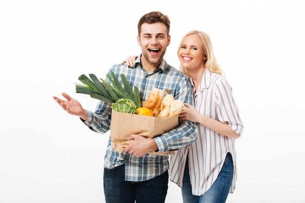 紙の買い物袋を保持している幸せなカップルの肖像画