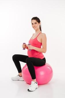 Молодая женщина делает упражнения с фитнес-мячом и гантелями