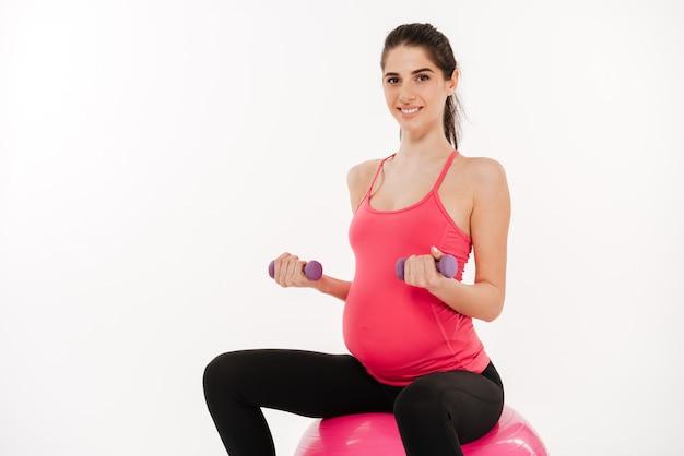 Беременная женщина делает упражнения с гимнастическим мячом и гантелями
