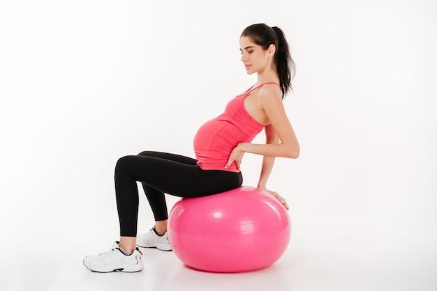 Портрет беременной женщины, сидящей на фитнес-мяче