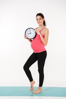 目覚まし時計を保持している笑顔の健康な妊娠中の女性の肖像画