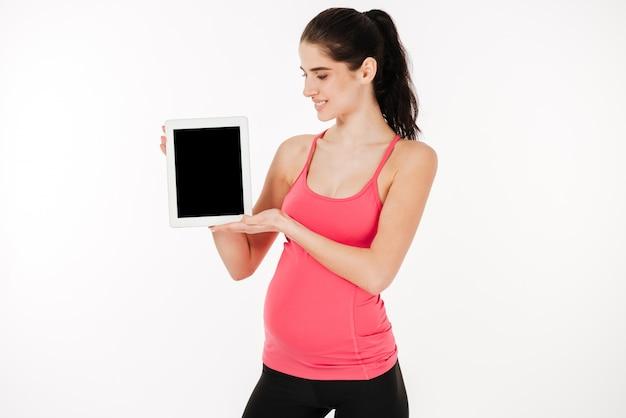 空白の画面のデジタルタブレットを示す笑顔の現代の妊娠中の女性