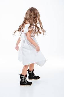立って踊っているかなり巻き毛の小さな女の子の完全な長さ