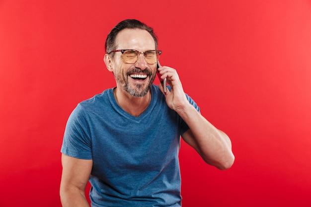 Портрет счастливый брюнетка человек, имеющий приятный мобильный разговор и говорить на смартфоне в студии, изолированных на красном фоне