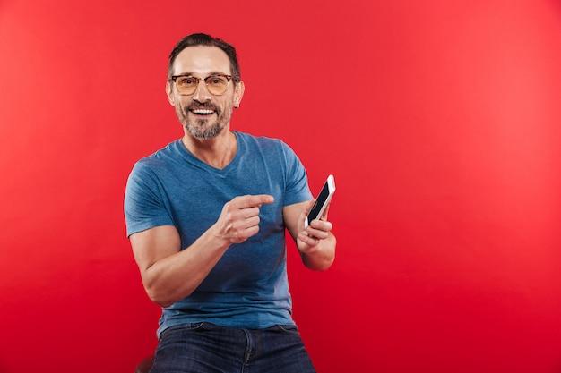 Взрослый веселый эмоциональный позитивный человек, с помощью мобильного телефона.
