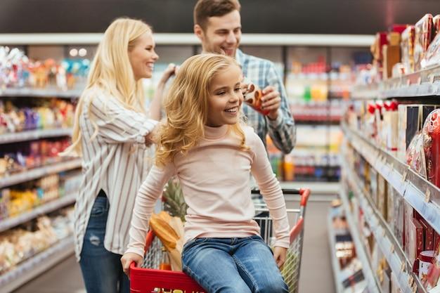 ショッピングカートに座っている陽気な少女