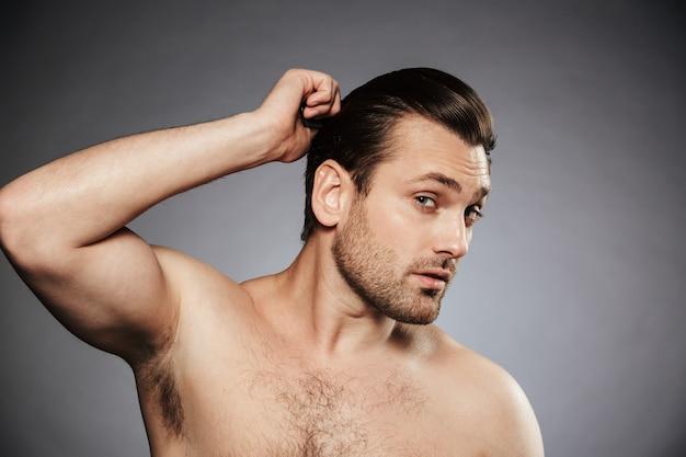 Портрет молодого человека без рубашки расчесывает волосы