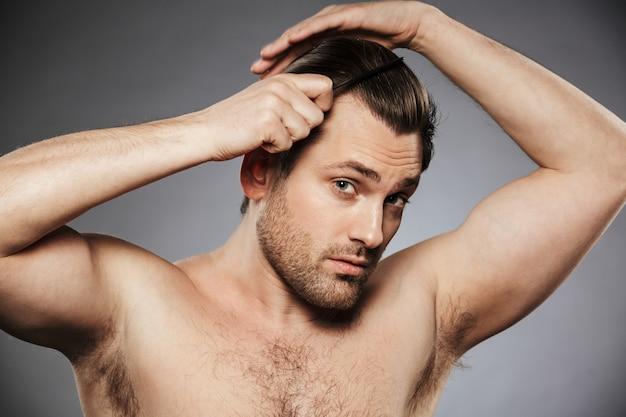 Портрет обаятельного мужчины без рубашки, расчесывающего волосы