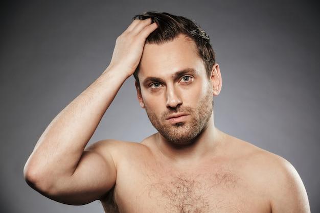 Портрет красивого мужчины без рубашки, поправляющего волосы