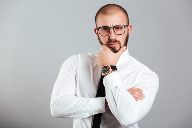 Изображение сконцентрированного взрослого человека в деловой одежде, касающегося его подбородка и позирующего с задумчивым взглядом, изолированного над серой стеной